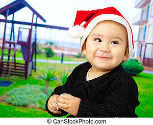 Baby boy smiling and wearing a christmas hat at a...
