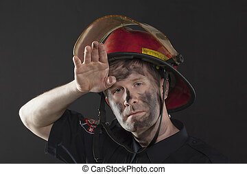 exhausted fireman - Exhausted Fireman wiping his dirty...