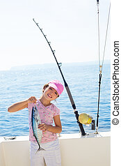 child little girl fishing in boat holding little tunny tuna...
