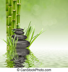 spa stones - zen basalt stones and bamboo in the water