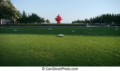 Red torch sculpture & Green grass.This public sculpture...