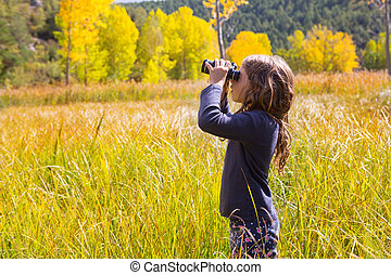 Explorer binocuar kid girl in yellow autumn nature -...