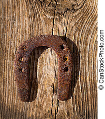 Antique horseshoe luck symbol rusted on vintage wood...