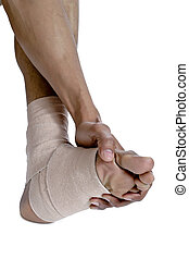 holding the injured foot with a bandage