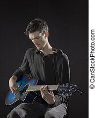 a male guitarist tuning the guitar - A male guitarist tuning...