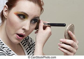 a woman applying eyeshadow