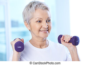Fitness - Portrait of pretty senior woman exercising with...