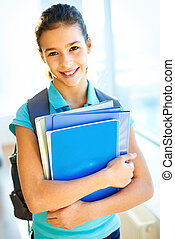 At school - Vertical portrait of a pretty student holding a...