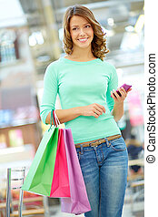 Girl with purchases - Vertical shot of a happy girl carrying...