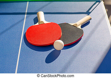 table tennis ping pong two paddles and white ball on blue...