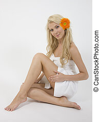 pretty model sitting with her legs crossed isolated on white...