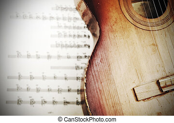 Acoustic guitar laying across sheet music