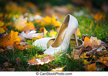 Bride's shoes on ground surrounded by golden autumn leaves...