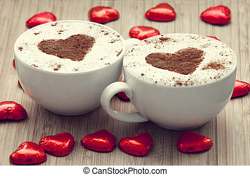 Two cup of coffee with heart symbol and candy around