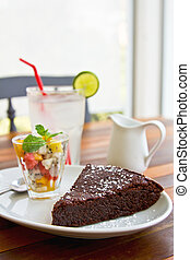 Chocolate fondant cake with fruit salad and lime juice