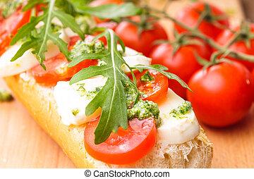 Sandwich with mozzarella, tomato, arugula and pesto