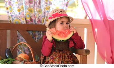 little girl eats a big piece of a water-melon with appetite