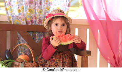 child eats a tasty water-melon, sitting on a summer verandah