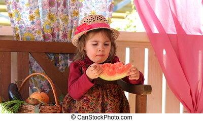 little girl sits on a verandah and eats  water-melon