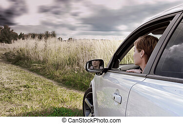 Woman driving car and looking on nature dark blue sky...