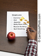 checking weight loss list - Image of checking weight loss...