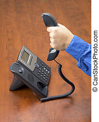 close up image of a person holding landline phone receiver -...