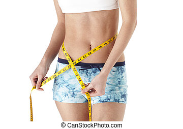 cropped image of a young woman measuring her waist - Cropped...
