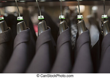 business suits hanging in clothing store - Close-up of...
