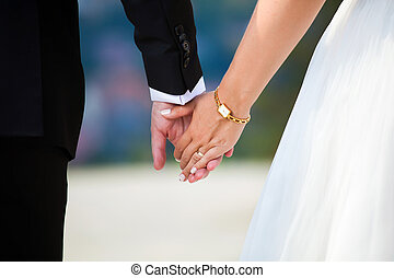 Young married couple holding hands on wedding day