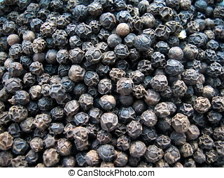 Whole black pepper closeup, full frame background