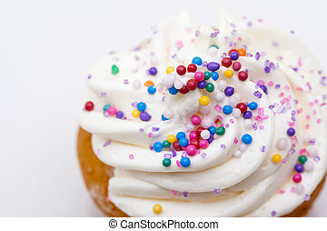 muffin decorated with white icing and sprinkles - Close-up...