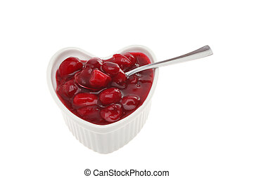 Cranberry sauce with whole fresh berries with a spoon in a...