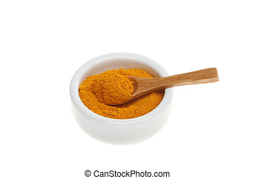 Tumeric spice with a wooden spoon in a ramekin isolated...