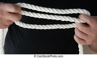 man ties sheepshank knot - a man ties a knot with a thick...