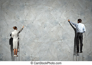 businesspeople drawing diagrams on wall - businesspeople...