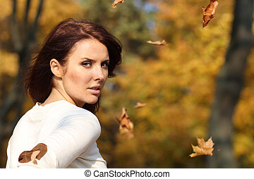 Portrait of a happy woman against yellow leaves