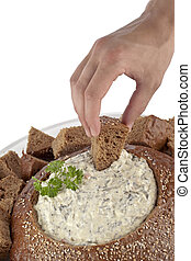 human hand with a cube on pumpernickel spinach dip