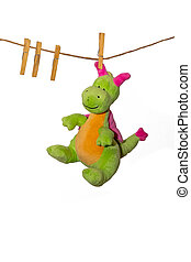 Soft toy a dragon dries on a linen rope