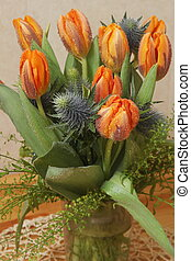 bunch of tulips and Eryngium or bur vertical high - bunch of...