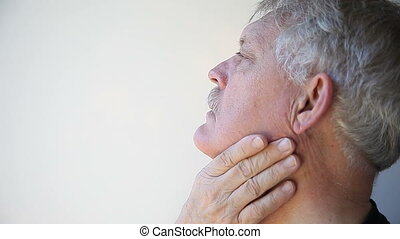 man with throat pain - senior man touches parts of his sore...