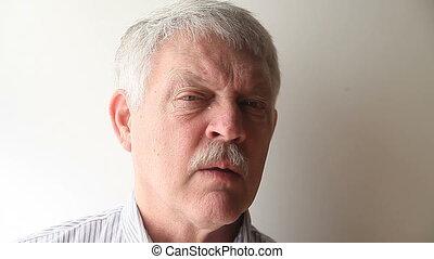 man sneezes - senior man sneezing