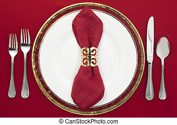 dinner setting - Dinner setting with silverware, red napkin...