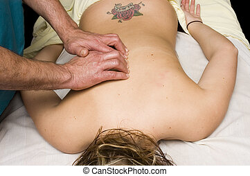 Woman having back massage from masseur