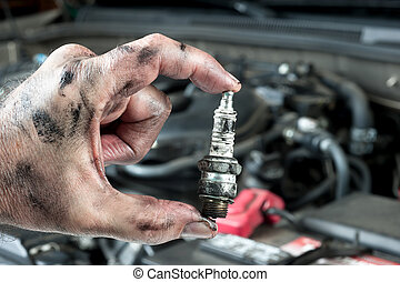 Auto mechanic and sparkplug - An auto mechanic holds an old,...