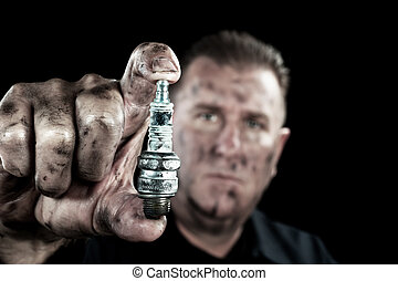 Auto mechanic and sparkplug - An automechanic shows a...