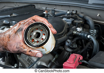 Auto mechanic holding oil filter - An auto mechanic shows an...