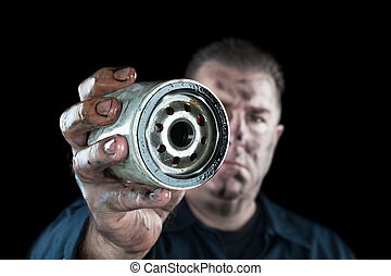 Oil Filter - An auto mechanic showing a dirty oil filter...