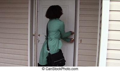Locking Door - Young woman locking front door and leaving