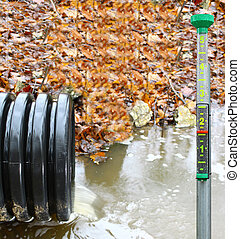 A waste water drainage pipe re-routing the water flow and polluting the environment at the same time with a rain gauge to show how much rain there was