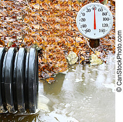 A waste water drainage pipe re-routing the water flow and polluting the environment at the same time with an outdoor thermometer showing the current temperature